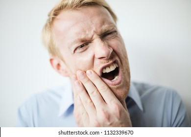Blond man having a toothache.