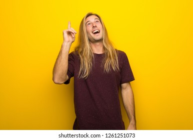 Blond man with long hair over yellow wall intending to realizes the solution while lifting a finger up