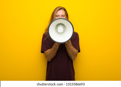 Blond man with long hair over yellow wall shouting through a megaphone to announce something