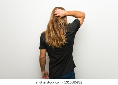 Blond man with long hair over white wall on back position looking back while scratching head