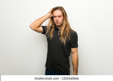 Blond man with long hair over white wall feeling upset