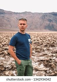 Blond man standing on salt rocks on Devil's Golf course in death Valley