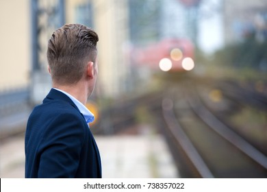 blond man in suit waiting at platform for the train