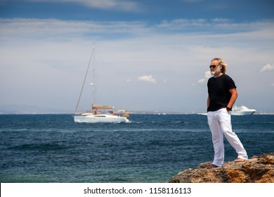 Blond man in white trousers, black t-shirt and sunglasses looking out over a Mediterranean seascape from the rocky coast.