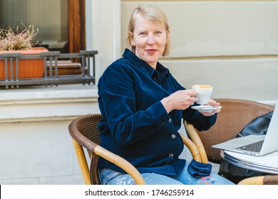 Blond mature scandinavian woman in cafe drinking coffee, using laptop. Your business proposal has just arrived. Smiling senior female open laptop in cafeteria terrace open air.