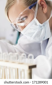 A blond medical or scientific researcher or doctor working in a laboratory