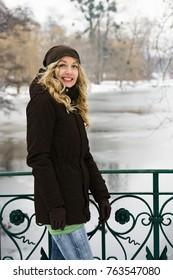 blond mid adult woman standing on bridge overlooking frozen river in winter