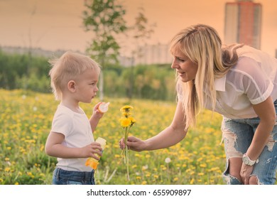 Blond mom and blond babe mom smiles. Outdoors in a clearing of flowers. sunny mood