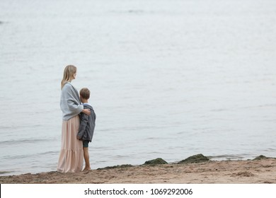 A blond mom in a long pink dress is wrapped up in a warm blanket hugging her young son, looking at the sea. view from the back.
