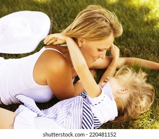 blond mother with daughter having fun on grass
