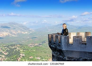 Blond on castle tower looking far away