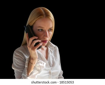 A Blond is on the phone against a black background. She looks worried or scared.