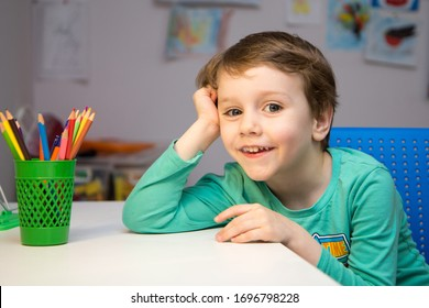 A blond preschooler sits at a white table with colored pencils in a green glass in his room and smiles into the frame. Draw houses during the period of isolation.