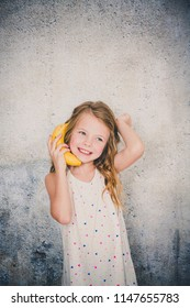 blond, Pretty girl is doing phone call with a banana