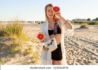 Blond pretty  woman posing with tasty grapefruit halves in hands. Wearing stylish glasses and boho beach outfit. Warm sunset colors. Shining  blonde hairs.