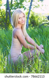 Blond resting in the garden at sunset
