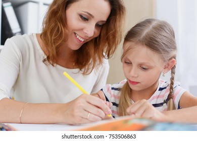 Blond smiling little girl hold in arm pencil drawing something together with mom. Beautiful female young artist minor baby-sitter art joy juvenile development parent lifestyle youth painter