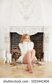 Blond smiling woman in long white knitted cozy sweater sitting at home near fire place.