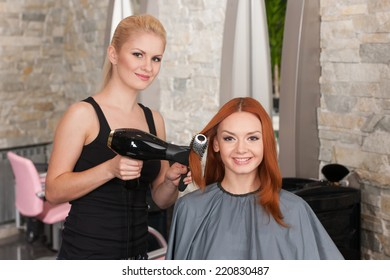 blond stylist drying redhead woman hair in salon. happy female giving new hair style to woman and looking into camera