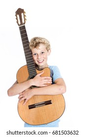 blond teen boy in blue holds guitar in studio against white background