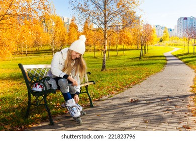 Blond teen girl with long hair in autumn park sitting on the bench and putting on roller blades
