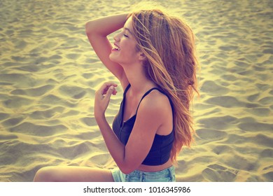 Blond teen girl portrait on the summer beach sand profile view