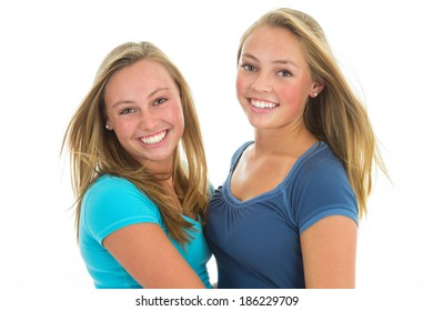 Blond teen sisters with beautiful smiles. Isolated on white background.