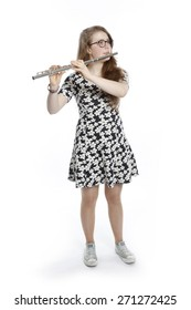 blond teenage girl with glasses plays the flute against white background