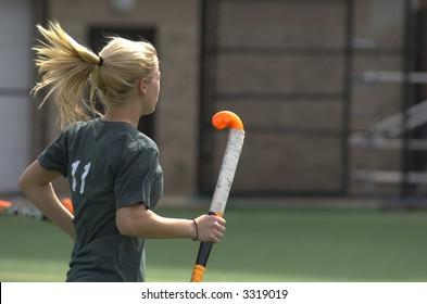 A blond, teenage girl runs across the field holding a bright orange field hockey stick.