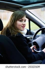 Blond teenage girl sitting in a car behind the wheel