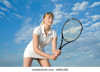 Blond tennis player with tennis racket on background of the sky