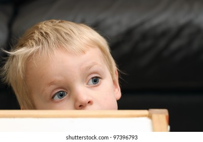Blond toddler boy behind a table