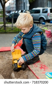Blond toddler boy playing in a sandbox with cityscape on a background