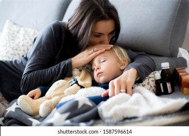 Blond toddler boy, sleeping on the couch in living room, lying down with fever, mom checking on him
