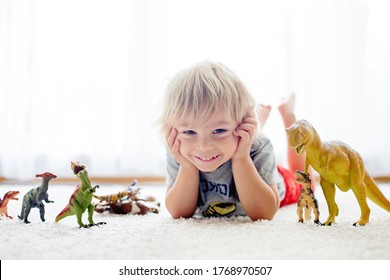Blond toddler child, playing with dinosaurs at home, nice soft baclk light