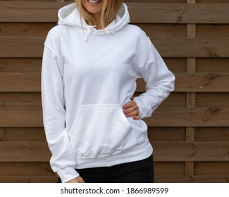 Blond unrecognizable woman wears white hoodie, she stands in front of camera. The empty space on her blouse in for design or inscription, for clothing mockup.  Sweatshirt template.