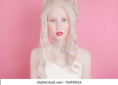 A blond woman with a beautiful luxurious rococo hair style in a white dress on a pink background.