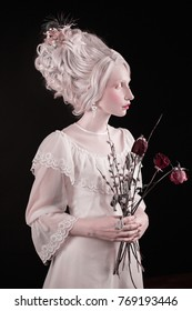 A blond woman with a beautiful luxurious rococo haircut in a white dress with flowers in her hand on a black background