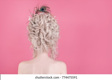 A blond woman with a beautiful luxurious rococo haircut in a white dress on a pink background.