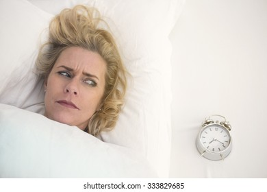blond woman in bed looking annoyed at her alarm clock