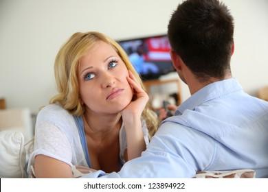 Blond woman being bored watching tv ith boyfriend