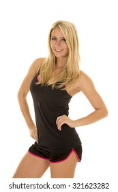 A blond woman with a big smile on her face in her fitness clothing.