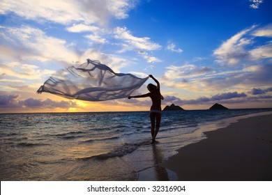 Blond woman in a bikini walking on the beach at sunrise with a chiffon scarf blowing  in the breeze