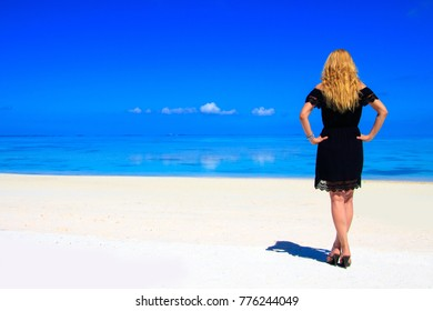 Blond woman with black dress on the sandy beach