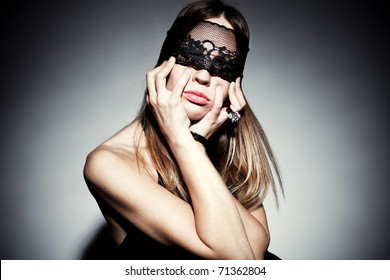 blond woman with black lace over eyes portrait, studio shot, horizobtal