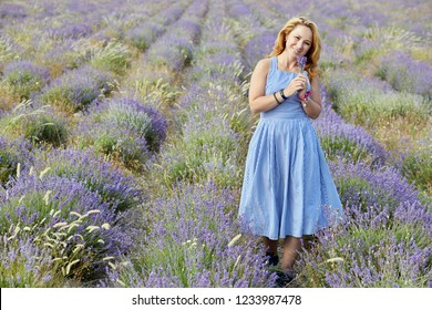 Blond woman in blue striped sundress on lavender field.