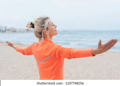 Blond woman celebrating being at the seaside standing facing the ocean with outstretched arms and close eyes as though meditating
