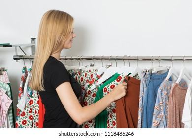 blond woman choosing clothes in a store