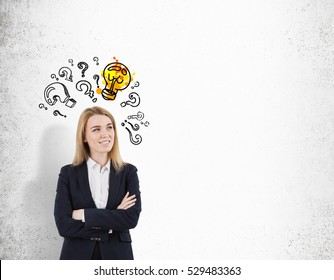 Blond woman with crossed arms is standing near a concrete wall with a glowing light bulb and question marks. Mock up