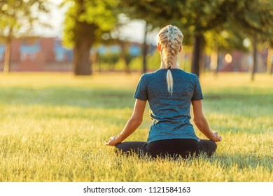 Blond Woman Doing Yoga In The Park
